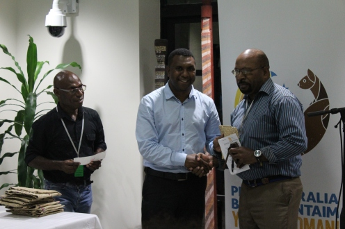 Mackhenly Kaiok of PNG Chamber of Mines and Petroleum presenting the Crocodile Prize and Cheque to John Kamasua